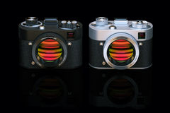 Two different photo cameras in black studio. 3D render Royalty Free Stock Images