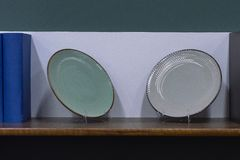Two different plates on the shelf in the living room. stock image