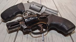 Two different revolvers on a wooden table. Two revolvers, a black 38 special and a stainless 44 spl together on a wooden table Royalty Free Stock Image