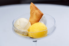 Two different scoops of ice cream with cake and passion fruit in a glass. Stock Image