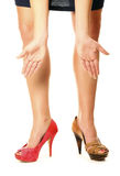 Two different shoes. A picture of a woman standing against white background in two different shoes stock image