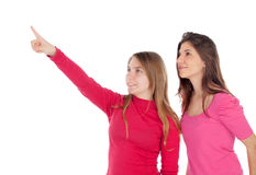 Two different sisters pointing something. Isolated on a white background Royalty Free Stock Photo