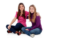 Two different sisters sitting on the floor Stock Images