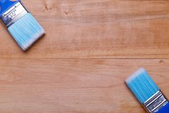 Two brushes in different angles point at each other against a wooden background. Two different in size blue brushes in different angles are directed at each Royalty Free Stock Photography