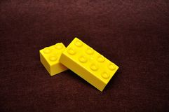 Two different size yellow building blocks. On a brown background royalty free stock photos