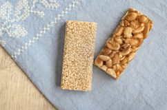 Two different types of gozinaki bars with peanuts and sesame seeds on a blue tablecloth background with embroidery on a wooden bac. Two different types of Stock Images