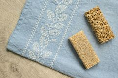 Two different types of gozinaki bars with sunflower seeds and sesame seeds on a blue tablecloth background with embroidery on a wo. Oden background Royalty Free Stock Images