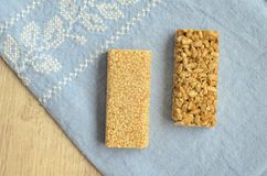 Two different types of gozinaki bars with sunflower seeds and sesame seeds on a blue tablecloth background with embroidery on a wo. Oden background Royalty Free Stock Image
