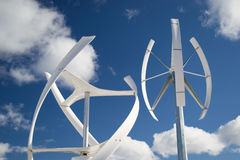 Wind energy. Two different types of windmill turbines generating wind power. A renewable energy source Royalty Free Stock Photo