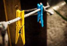 Two different wash pins yellow and blue hanging on rope on vinta Stock Photos