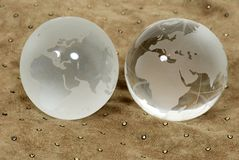 Two different worlds. Shown by contrasting crystal globes on a leather background royalty free stock photo