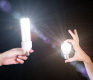 Two differrent light bulbs in hands isolated. On black background Royalty Free Stock Photography