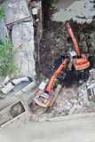 Two diggers moving soil onto truck. Aerial view of a construction site in Mumbai, India, two diggers working together to move soil onto a tipper truck Royalty Free Stock Photography