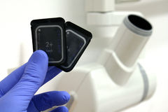 Two digital dental radiograpphy (RVG) sensors and x-ray tube head. Two digital dental radiograpphy (RVG) sensors in left hand with blue surgical glove Stock Photo