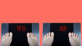 Two digital scales with female feet on them and red signs yes and no. Concept of weight control before and after. Two digital scales with female feet on them stock images
