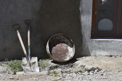 Two dirty big spades, a gray round bowl leaned against the clay wall of the village house, to the right wooden window, a white rou. Two dirty big spades, a gray Stock Images