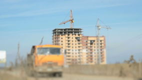 Two dirty truck traveling on the road.Construction. Two dirty trucks driving on the road in the background on the construction of apartment buildings stock footage