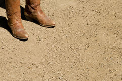 Two dirty western cowboy boots standing on dirt ground Royalty Free Stock Images