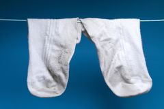 Two dirty white old sock weigh on the rope. blue background. royalty free stock images