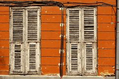Two Dirty Wooden Closed Shutters In The Old Building Facade. Wall  With Many Electric Wires And Rainwater Pipe Stock Photography