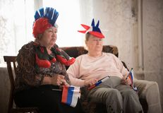 Two disappointed elderly women watching TV in russian accessories royalty free stock image