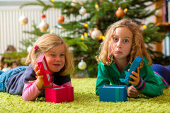 Two disappointed girls with christmas presents Royalty Free Stock Photos