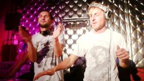 Two Disc Jockey dancing entertaining visitors nightclub discos near sound equipment stock video footage