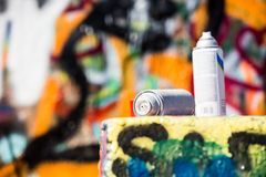 Two Discarded Spray Cans in Front of Graffiti Wall. Used paint cans near a wall with graffiti Royalty Free Stock Photos