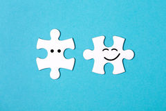 Two disconnected jigsaw puzzle pieces. On blue background. One piece is happy to connect and another one is surprised. The concept of finding the right Royalty Free Stock Photo