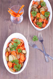 Two dishes with baked potatoes and carrots Royalty Free Stock Images