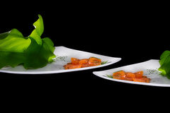 Tomato Salad. Creative Cuisine. Two dishes with sliced cherry tomatoes and large green leaves Royalty Free Stock Photos