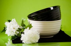 Two dishes with spring flowers on green Stock Image