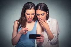 Two displeased women looking at mobile phone stock photo