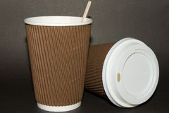 Two disposable cups for hot drinks on a dark backgrounds. Paper cups and white cap with the inscription Caution Contents Hot! . Two disposable cups for hot stock image