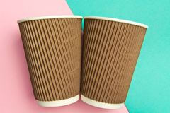 Two disposable cups for hot drinks on a geometric pink and turquoise backgrounds. Paper cups.  stock images