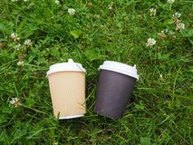 Two disposable paper coffee cups lie on the ground among the clover and green grass. royalty free stock image