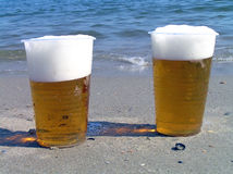 Two disposable plastic glasses with beer. Royalty Free Stock Photos