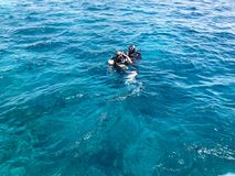 Two divers in black diving waterproof suits with shiny metal aluminum canisters float, immerse in blue sea water on vacation, crui royalty free stock image