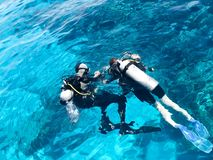 Two divers in black scuba diving suits, a man and a woman with oxygen bottles sink under the transparent blue water in the sea, th royalty free stock photo