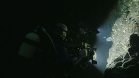 Two divers filming near stony wall in the cenote, Cuba stock footage
