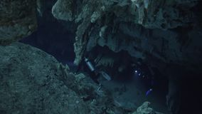 Divers in cave. Two divers underwater with flashligh swiming through stalagmite in cenote cave dos ojos stock footage