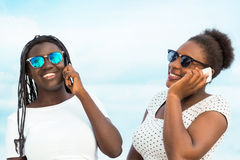 Two diverse african teens talking on smart phones. Close up portrait of two diverse african teen girls wearing sun glasses talking on smart phones outdoors Royalty Free Stock Photo