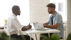 Two diverse businessmen shaking hands negotiating at meeting in office. African american and caucasian diverse businessmen shaking hands negotiating at meeting stock video