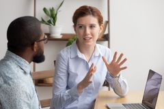 Free Two Diverse Businesspeople Chatting Sitting Behind Laptop In Office Stock Image - 149438831