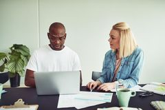 Two diverse coworkers talking together while working on a laptop. Two diverse businesspeople talking together while sitting at a desk in an office working on a stock image