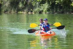 Two diverse little boys kayaking down a beautiful river Stock Photo