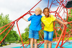 Two diverse looking boys stand close on red web Royalty Free Stock Photography
