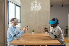Two diverse man in casual wear are developing a project using virtual reality goggles. royalty free stock photos