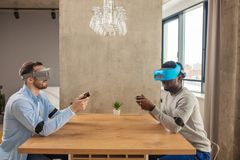 Two diverse man in casual wear are developing a project using virtual reality goggles. royalty free stock photo