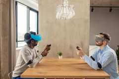 Two diverse man in casual wear are developing a project using virtual reality goggles. royalty free stock image